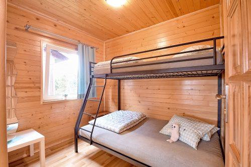 Sypialnia z piętrowym łóżkiem w domku letniskowym